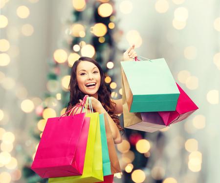 shopping: bán, quà tặng, ngày lễ và người khái niệm - mỉm cười với người phụ nữ túi mua sắm đầy màu sắc qua phòng khách và nền cây Giáng sinh