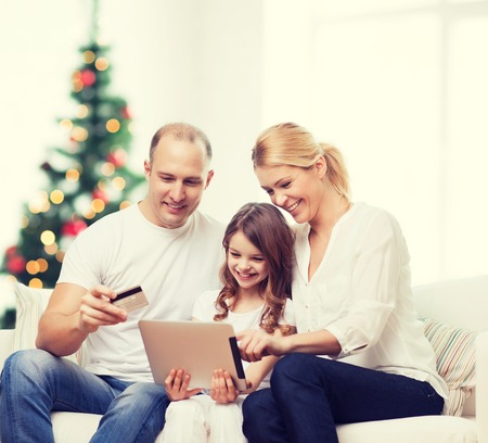 beautiful preteen girl: family, holidays, technology and people - smiling mother, father and little girl with tablet pc computers over living room and christmas tree background Stock Photo