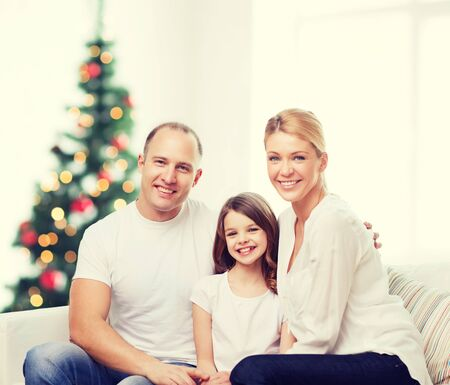 girl bonding: family, childhood, holidays and people - smiling mother, father and little girl over living room and christmas tree background