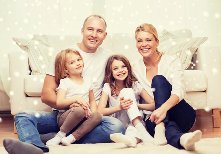 girl bonding: family, childhood, people and home concept - smiling parents with two little girls sitting on floor at home