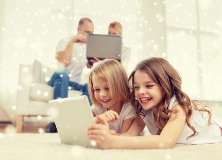 가족, 가정, 기술과 사람 - 눈송이 배경에 태블릿 pc 컴퓨터와 함께 어머니, 아버지와 어린 소녀 미소