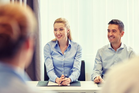 happy workers: business, people and teamwork concept - group of smiling businesspeople meeting in office Stock Photo