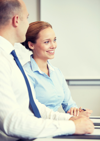 office meeting: business, people and teamwork concept - smiling businessman and businesswoman meeting in office