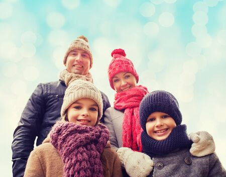 childhood: family, childhood, season and people concept - happy family in winter clothes over blue lights background