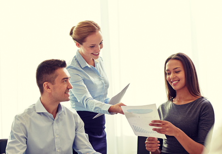 discussing: business, people and teamwork concept - smiling business team with papers meeting in office
