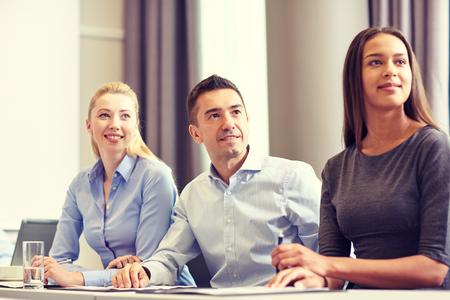 utbildning: företag, människor och lagarbete koncept - grupp leende businessmöte mot uppvisande kontor