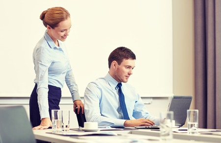 secretary desk: business, people and work concept - businessman and secretary with laptop working in office Stock Photo