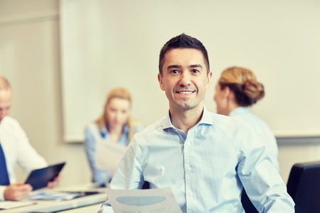 working in office: business, people and teamwork concept - smiling businessman with group of businesspeople meeting in office Stock Photo