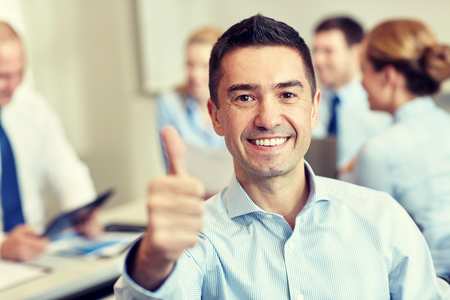 thumbs: business, people, gesture and teamwork concept - smiling businessman showing thumbs up with group of businesspeople meeting in office