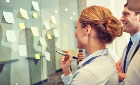 trabajadores: negocios, personas, trabajo en equipo y la planificación concepto - sonriendo equipo de negocios con marcador y pegatinas que trabaja en oficina