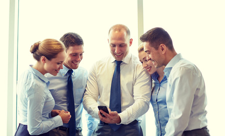 Online Business: business, teamwork, people and technology concept - business team with smartphone meeting in office