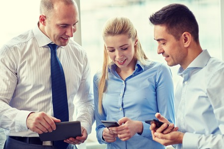 mobile business: business, teamwork, people and technology concept - business team with tablet pc computer and smartphones meeting in office Stock Photo