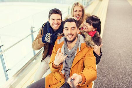 young group: people, friendship, technology and leisure concept - happy friends taking selfie with camera or smartphone and selfie stick on skating rink