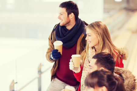 ice arena: people, friendship, hot drinks and leisure concept - happy friends drinking from paper coffee cups on skating rink