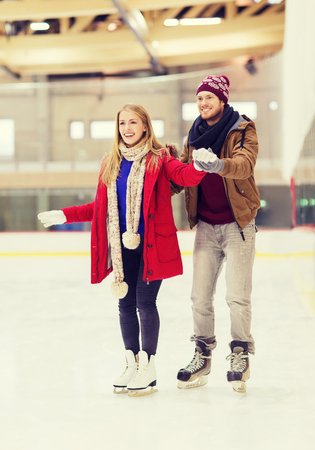 sport and leisure: people, friendship, sport and leisure concept - happy couple on skating rink Stock Photo