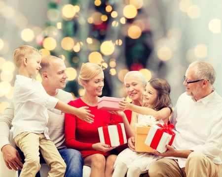 femmes souriantes: family, holidays, generation, christmas and people concept - smiling family with gift boxes sitting on couch over tree lights background