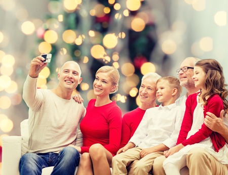 holidays: family, holidays, generation, christmas and people concept - smiling family with camera taking selfie and sitting on couch over tree lights background Stock Photo