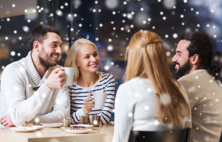 christmas table: people, leisure, communication, season and concept - happy friends meeting and drinking tea or coffee at winter cafe