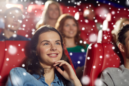 winter theater: cinema, entertainment and people concept - happy woman watching comedy movie in theater over snowflakes