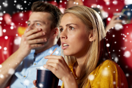 christmas movies: cinema, entertainment and people concept - terrified couple drinking soda and watching horror, drama or thriller movie in theater