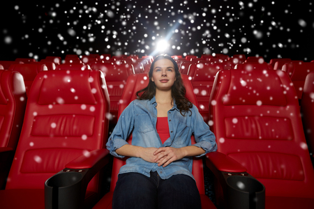 winter theater: cinema, entertainment and people concept - young woman watching movie alone in empty theater auditorium over snowflakes