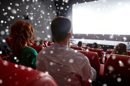 at leisure: cinema, entertainment, leisure and people concept - couple watching movie in theater from back over snowflakes Stock Photo
