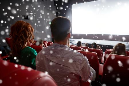teatro: el cine, el entretenimiento, el ocio y el concepto de la gente - película pareja viendo en el teatro desde atrás sobre los copos de nieve