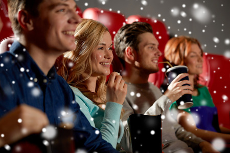 christmas movies: cinema, entertainment and people concept - happy friends with popcorn and lemonade drinks watching movie in theater with snowflakes