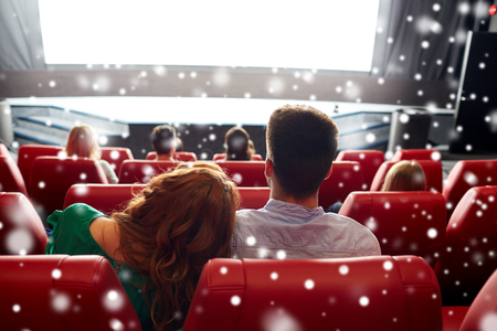 back screen: cinema, entertainment, leisure and people concept - happy couple watching movie in theater from back over snowflakes