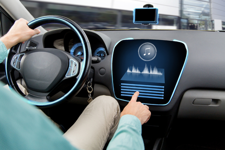 equipo de sonido: el transporte, la tecnología moderna, la música y el concepto de la gente - cerca del hombre que conduce el coche con el sistema de audio estéreo ordenador de a bordo