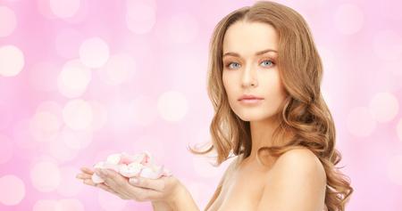 la belleza, la gente, las vacaciones, la piel y el concepto de cuidado del cuerpo - mujer joven hermosa con pétalos de flores rosas y los hombros al descubierto más de luces de color rosa de fondo