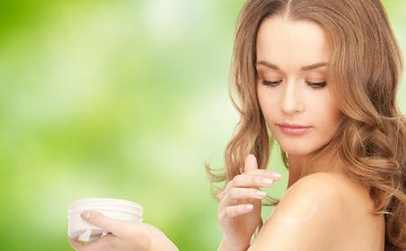 schoonheid, mensen en gezondheid concept - mooie glimlachende vrouw schoon gezicht huid met katoen blok op blauwe achtergrond