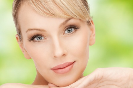 natural face: beauty, people and makeover concept - beautiful young woman face over green natural background