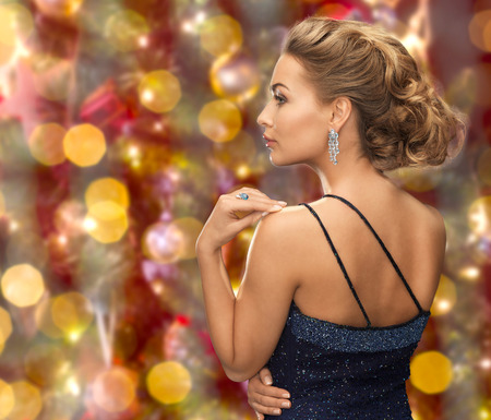 people, holidays, jewelry and glamour concept - beautiful woman with diamond earring over christmas lights background