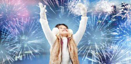 asian preteen: winter, holidays, children and people concept - happy little girl wearing earmuffs over firework background