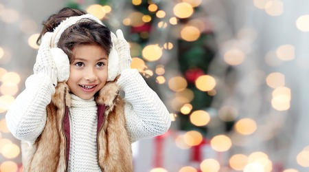 asian trees: winter, people, childhood and happiness concept - happy little girl wearing earmuffs over christmas tree lights background Stock Photo