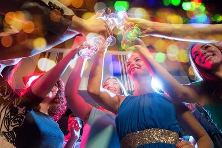bebiendo vino: fiesta, días de fiesta, celebración, vida nocturna y concepto de las personas - mujeres felices con los vidrios clincing de champán sin alcohol en el club