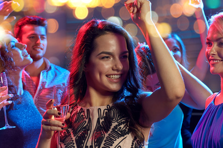 party night: party, holidays, celebration, nightlife and people concept - happy friends with glasses of non-alcoholic champagne dancing at disco in nightclub