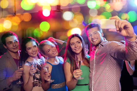 prom: party, holidays, technology, nightlife and people concept - smiling friends with glasses of non-alcoholic champagne and smartphone taking selfie in club