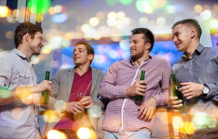 party night: nightlife, party, friendship, leisure and people concept - group of smiling male friends with beer bottles drinking in nightclub