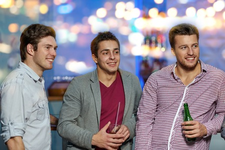 man looking out: nightlife, party, friendship, leisure and people concept - group of smiling male friends with beer bottles drinking in nightclub