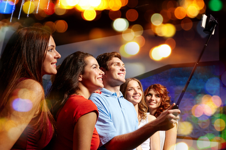 night out: party, technology, nightlife and people concept - smiling friends with smartphone and monopod taking selfie in club