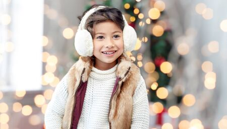 asian style: winter, people, childhood and happiness concept - happy little girl wearing earmuffs over christmas tree lights background Stock Photo