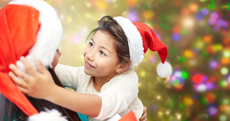 asian preteen: christmas, family, childhood and people concept - happy mother and little girl in santa hats over holidays lights background Stock Photo