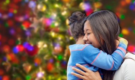 asian preteen: family, children, love and happy people concept - happy mother and daughter hugging over lights background