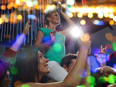 take time out: party, holidays, celebration, nightlife and people concept - smiling friends with smartphone taking picture and waving hands at concert in club Stock Photo