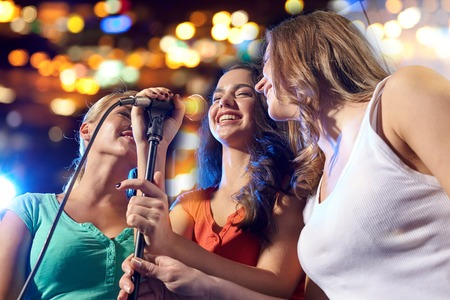 singing: party, holidays, celebration, nightlife and people concept - happy young women singing karaoke in night club