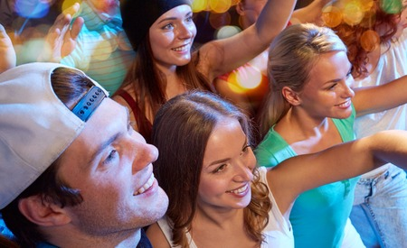 teen couple: party, holidays, celebration, nightlife and people concept - smiling friends waving hands at concert in club
