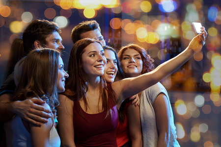 take time out: party, technology, nightlife and people concept - smiling friends with smartphone taking selfie in club