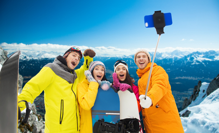 group picture: winter sport, leisure, friendship, technology and people concept - happy friends with snowboards and taking picture by smartphone on selfie stick over snowy mountains background